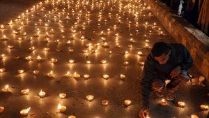 Kouluiskussa kuolleiden muistoksi sytytettyjä kynttilöitä.