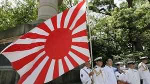 Laivaston sotilaat Japanin lipun kanssa muistomerkillä