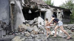 Lapset tutkivat kotinsa vieressä olevan kranaattitulessa tuhoutuneen talon raunioita Donetskissa