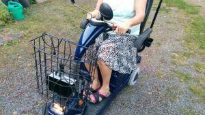 Nainen ajaa invamopoa ulkona.