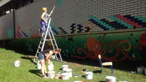 Mies maalaa tikkailla ja nainen avaa maalipurkkia