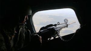 Mies suuren konekiväärin kanssa lentokoneen tai helikopterin tähystysakolla.