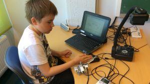 Poika ohjelmoi robottia
