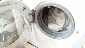 Kuvassa pesikone, jonka luukku on auki:koneessa valkoista lakanapyykkiä.