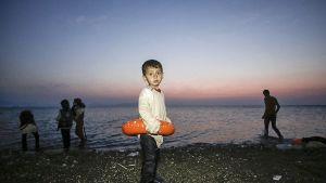 lapsi seisoo rannalla pelastusrengas ympärillään