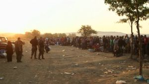 sotilaita ja pakolaisia tienvarressa