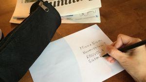 käsi kirjoittaa kirjeeseen osoitetta