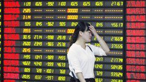Pörssityöntekijä kävelee infotaulun ohi  24. elokuuta Huabeissa.