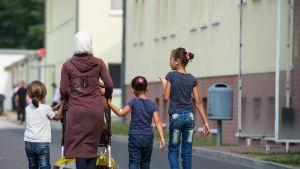 Pakolaisperhe – äiti lapsineen – kävelee turvapaikanhakijoiden käsittelykeskuksen ulkopuolella Saksan Eisenhüttenstadtissa.