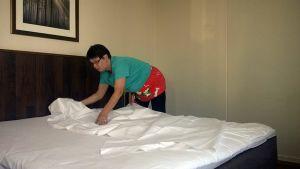 Kerrosvastaava Merja Salonen petaamassa sänkyä.