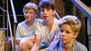 kolme poikaa istuu rappusilla