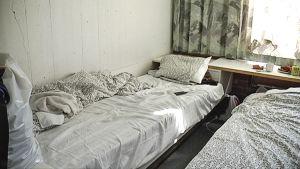 Kuvassa kahden sängyn huone, jossa muuta liikkumatilaa on erittäin vähän.