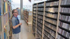 Reijo Holm tarkastelee Kokkolan kirjaston musiikkiosastolla hyllyjän välissä.