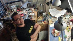 Mies poseeraa  työhuoneessa, joka täynnä erilaisia työvälineitä ja osia.
