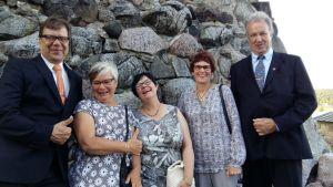 Viisi ihmistä nauraa näyttävästi Hämeen vanhan linnan muurien edessä