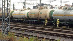 Palomiehet kävelevät junavaunun vierellä.
