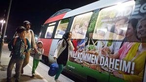 """Iranista lähtenyt perhe on Nickelsdorfin kaupungin asemalla matkalla Wieniin Itävallassa  31. elokuuta. Junan kyljessä olevassa mainoksessa lukee """"Tervetuloa kotiin""""."""
