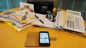 Pöydällä tavaroita, jotka älypuhelin on korvannut.