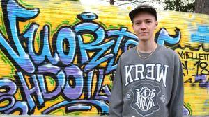 Kajaanilainen graffittaituri Eetu Schroderus ja kelmuun tehty teos.