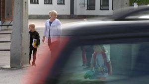 Auto ajaa suojatien yli, koululaiset odottavat tien toisella puolen.