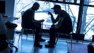 Kaksi miestä tiukassa keskustelussa.