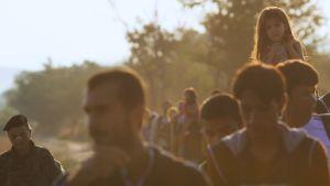 Pakolaisia ylittämässä jonossa rajaa.