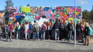 Tornion Putaan koulun oppilaita maalaamassa graffitiseinää.