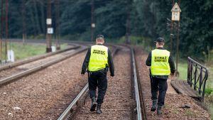 Kaksi poliisia vartijaa junaraiteilla.