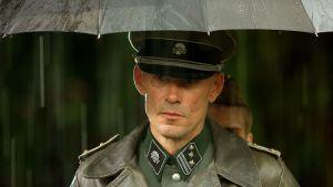 Mies seisoon natsiupseerin asusssa sateenvarjon alla sateessa