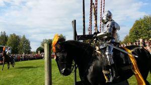Kaksi haarniskoihin pukeutunutta ratsukkoa turnajaiskentällä