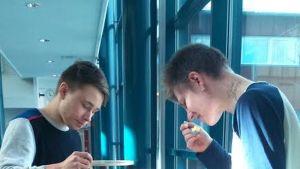 Kaksi opiskelijaa  syövät seisaallaan.