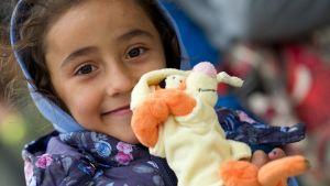 Hymyilevä pikkutyttö esittelee Tikru-pehmoleluaan.