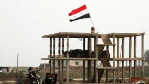 Syyrian lippu raunioituneen rakennuksen katolla.