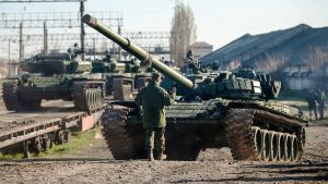 Mies ja panssarivaunu ja useita panssareita junavaunujen kyydissä.