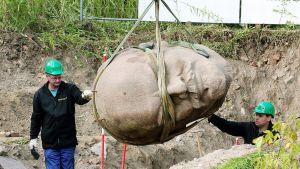 Suurta pään patsasta nostetaan maasta.