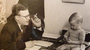Vanha valokuva, jossa aikuinen mies katsoo pöydän yli pientä poikaa.