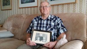 Bo Nyström istuu sohvalla vanha valokuva käsissään. Kuvassa ovat hän, veljensä ja veljen Ruotsin kodin poika.