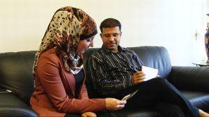 Irakilaisperheen mies ja vaimo istuvat sohvalla.
