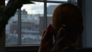 Puhelimeen puhuvan naisen silhuetti ikkunaa vasten.