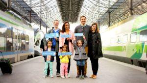 Kaksi perhettä rautatieasemalla.