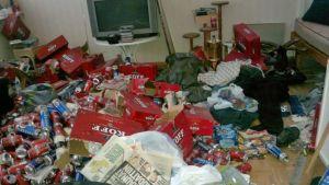 Huoneen lattialla on paljon roskia, tölkkejä ja lehtiä.