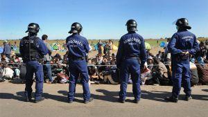 Neljä poliisia ja pakolaisia.