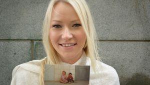 Hanna Hukka pitelee vanhaa valokuvaa.