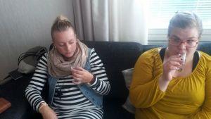 Milla Häkkinen ja Sofia Saarinen istuvat sohvalla ja maistelevat terveysjuomaa.