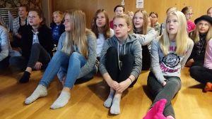 Alakoululaisia istuu luokan lattialla.