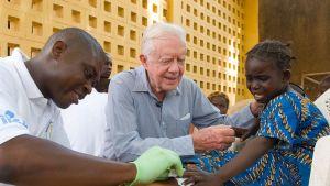Yhdysvaltain entinen presidentti  Jimmy Carter rauhoitteli tyttöä jonka jalasta poistettiin matoa Savelugussa, Ghanassa vuonna 2007.