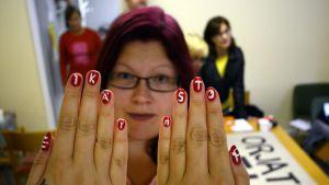 """Nainen näyttää kynsiään, joissa lukee """"Ei käy"""" ja """"Stop""""."""