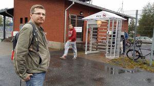 Kuvassa Petri Partanen  suurteollisusualueen portilla, taustalla tiilinen rakennus.