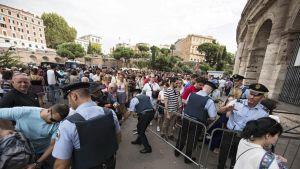 Tuhannet turistit jonottavat Colosseumin ulkopuolella.