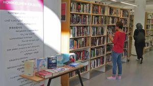 Kuva kirjastosta, etualalla kirjaston kyltti, taustalla nainen hyllyn ääressä.